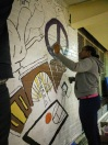 ServiceWorks Scholar Dachanna helping to color in the new gym mural!